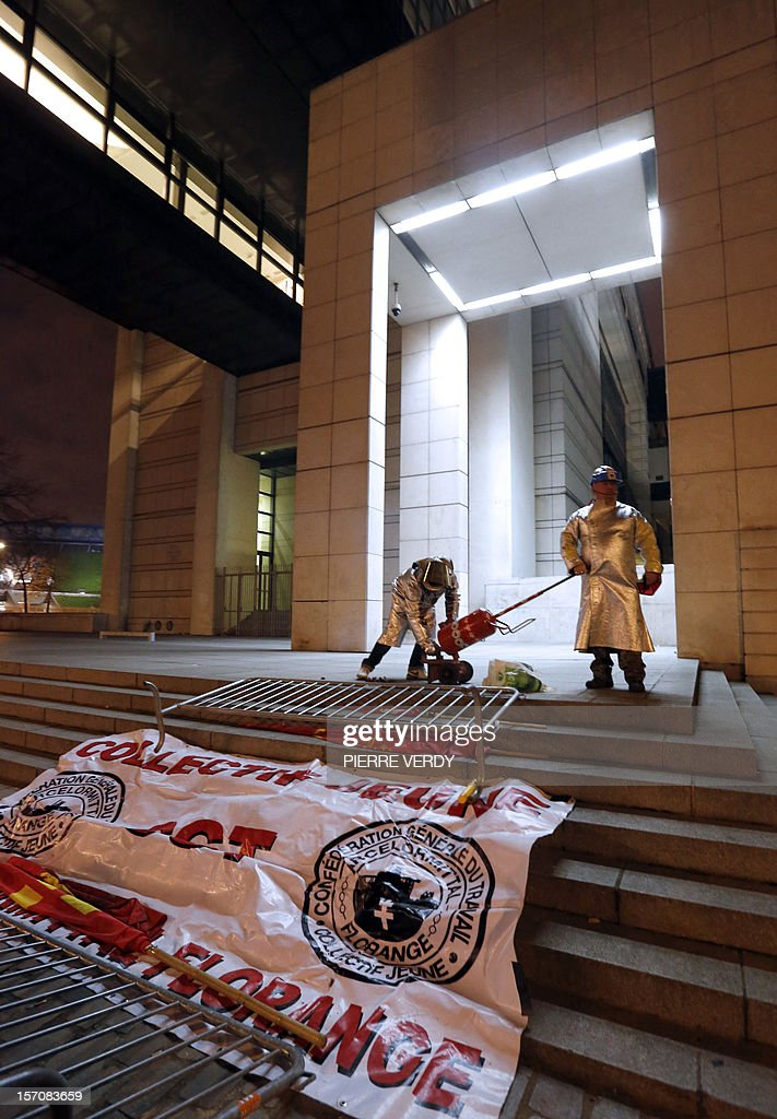 Arcelor-Mittal employees deploy a banner in front of the ministry as the group's unionists meet French Minister for Industrial Renewal on November 28, 2012. France said today it had an investor willing to invest 400 million euros ($515 million) in a steel plant at the centre of a bitter row between the government and its owner ArcelorMittal.