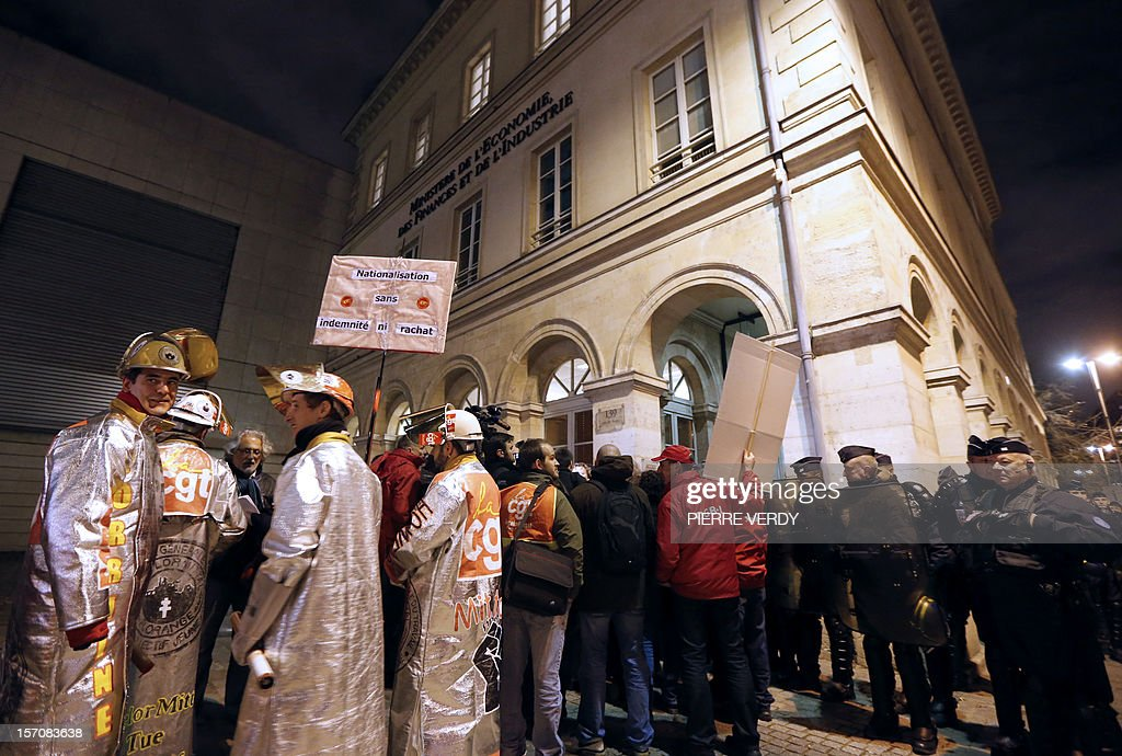 Arcelor-Mittal employees gather in front of the ministry near riot policemen as the group's unionists meet French Minister for Industrial Renewal on November 28, 2012. France said today it had an investor willing to invest 400 million euros ($515 million) in a steel plant at the centre of a bitter row between the government and its owner ArcelorMittal.