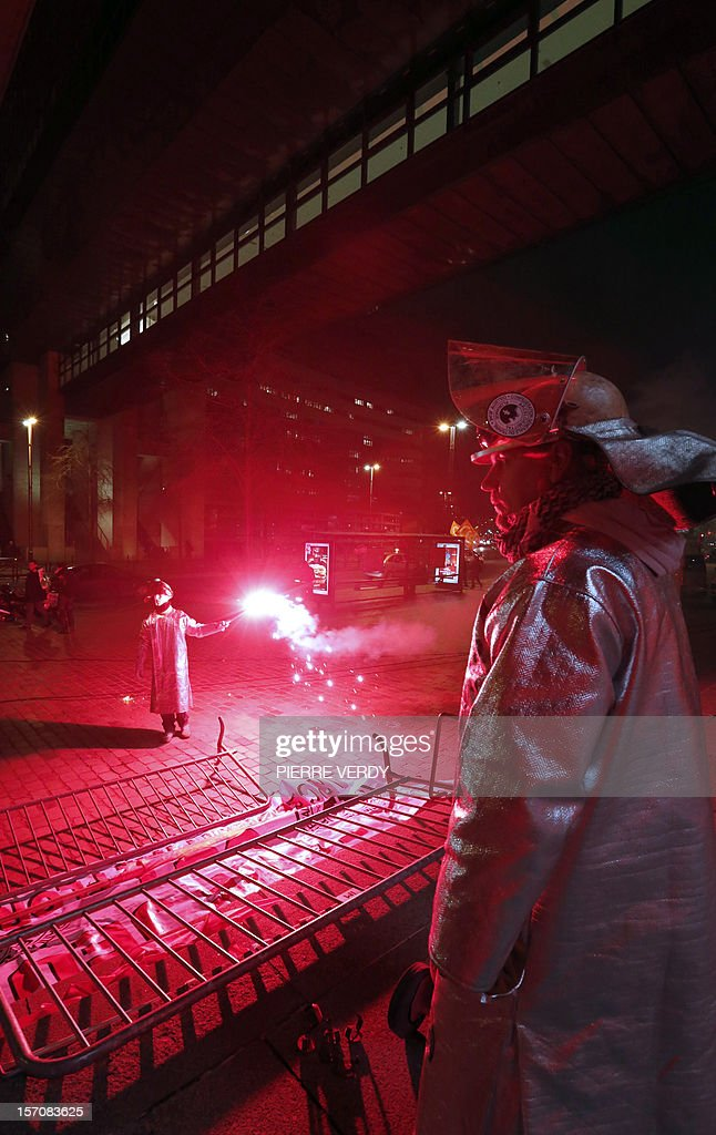 Arcelor-Mittal employees hold smoke devices in front of the ministry as the group's unionists meet French Minister for Industrial Renewal on November 28, 2012. France said today it had an investor willing to invest 400 million euros ($515 million) in a steel plant at the centre of a bitter row between the government and its owner ArcelorMittal.