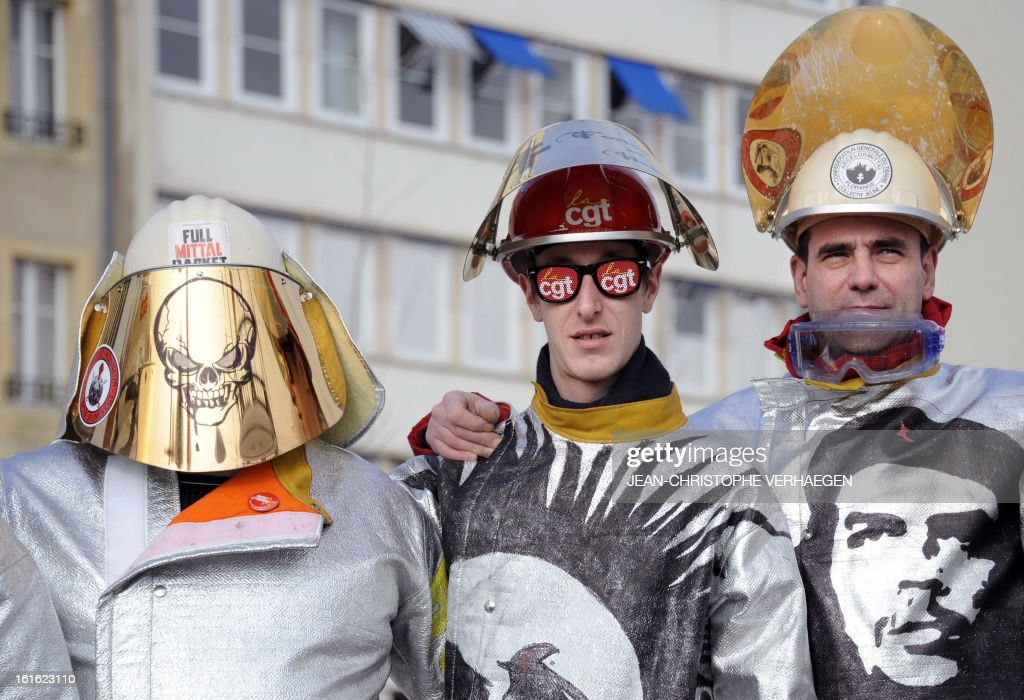 ArcelorMittal workers wearing steelmaker helmets and clothes pose during a demonstration called by French CGT trade union on February 13, 2013 in Metz, eastern France, to claim for the safeguard of the local industry in the French eastern region of Lorraine. AFP PHOTO / JEAN-CHRISTOPHE VERHAEGEN