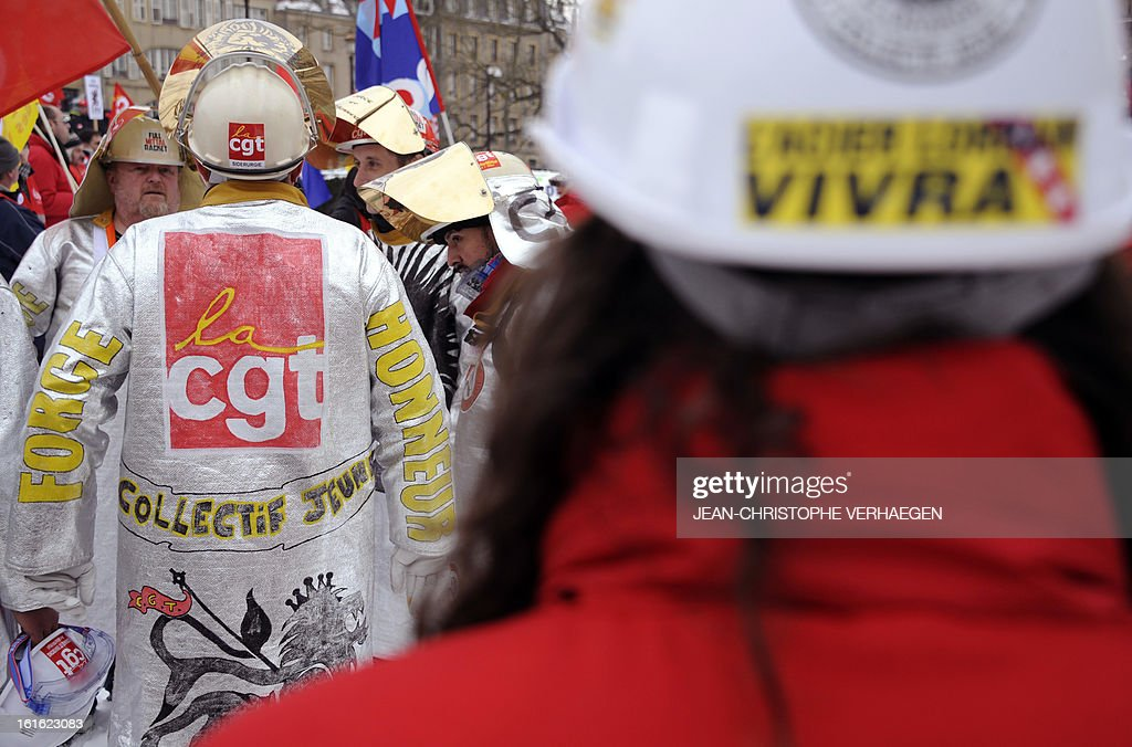 ArcelorMittal workers wearing steelmaker helmets and clothes (L) take part in a demonstration called by French CGT trade union on February 13, 2013 in Metz, eastern France, to claim for the safeguard of the local industry in the French eastern region of Lorraine.