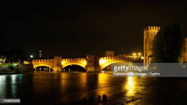Arch Bridge Over River Against Sky In City At Night