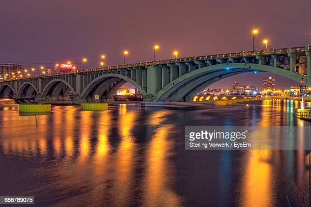 Arch Bridge Over River With Orange Lights Reflection At Night