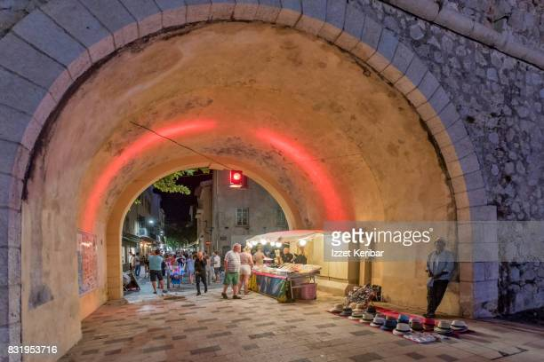 Arch under the old town walls at Antibes, street vendor at corner,France