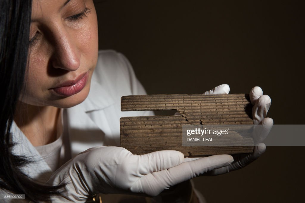 archaeologist Luisa Duarte poses with a Roman waxed writing tablet dated AD 60/162 what appears to show the last two lines the alphabet at...