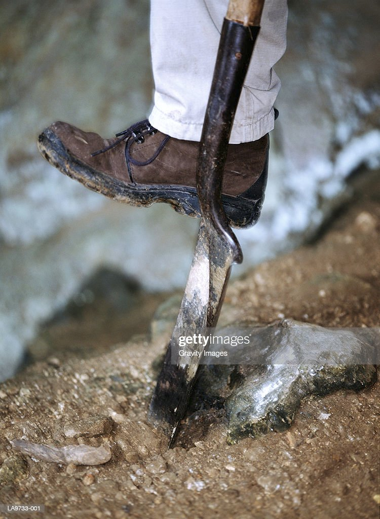 Archaeologist using spade, low-section : Stock Photo