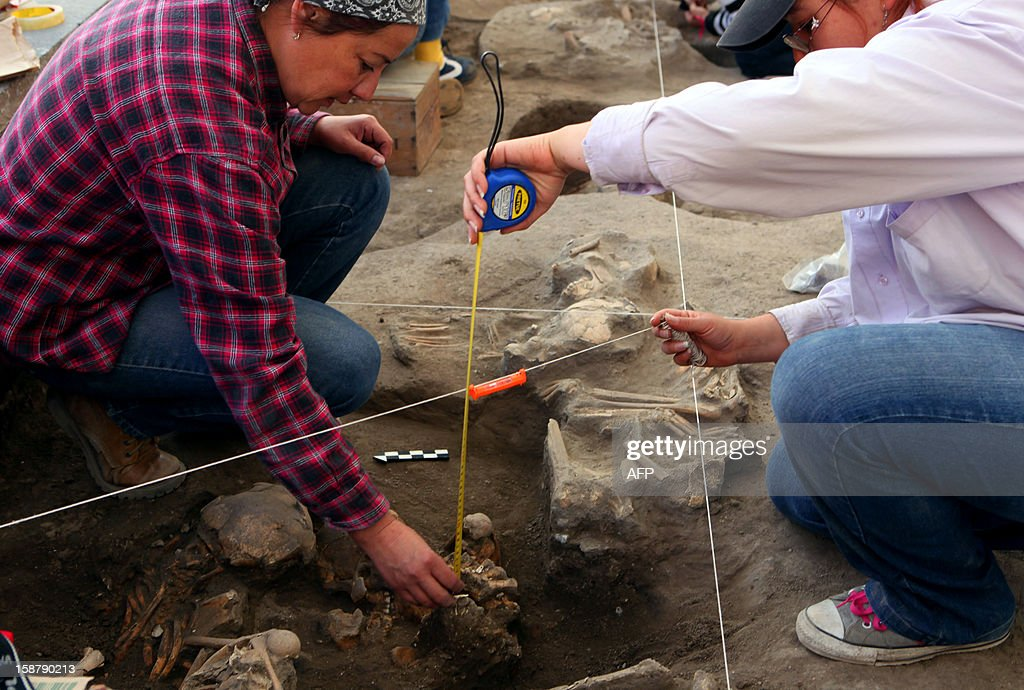 Archaeologists excavate the bones of twelve bodies December 28, 2012 in Cholula, a town 120 kilometers north of the Mexican capital. Archeologists in central Mexico uncovered the bones of 12 children and adults who may have been buried 800 years ago, a National Institute of Anthropology and History expert told AFP. The skeletons were discovered as the archeologists supervised the installation of a new drain in an old neighborhood of Cholula. AFP PHOTO/Jose Castanares