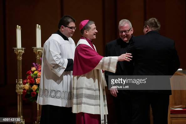 Archbishop Blase Cupich shares a laugh with Fr Dan Costello and Fr Louis Tylka after Cupich received his Archdiocesan stole at his installation to...