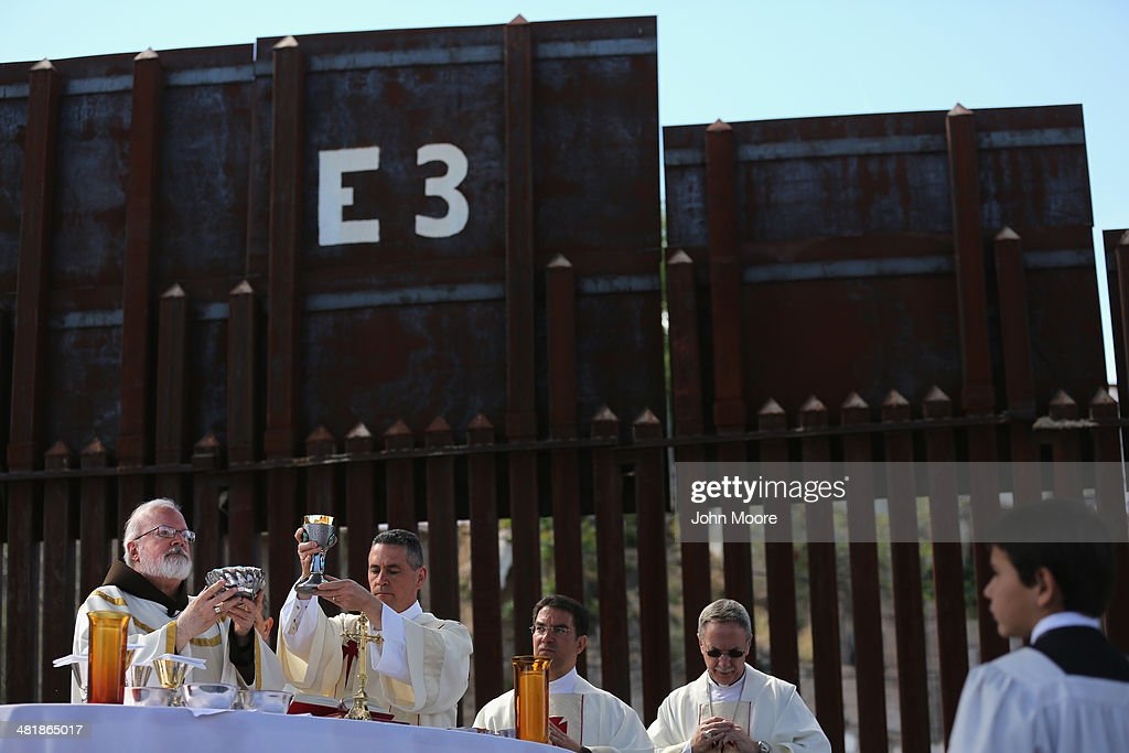 Archbishop of Boston Cardinal Sean O'Malley (L), celebrates communion next to the U.S.-Mexico border fence during a special 'Mass on the Border' on April 1, 2014 in Nogales, Arizona. Catholic bishops led by Cardinal O'Malley held the mass at the border fence to pray for comprehensive immigration reform and for those who have died along the border.