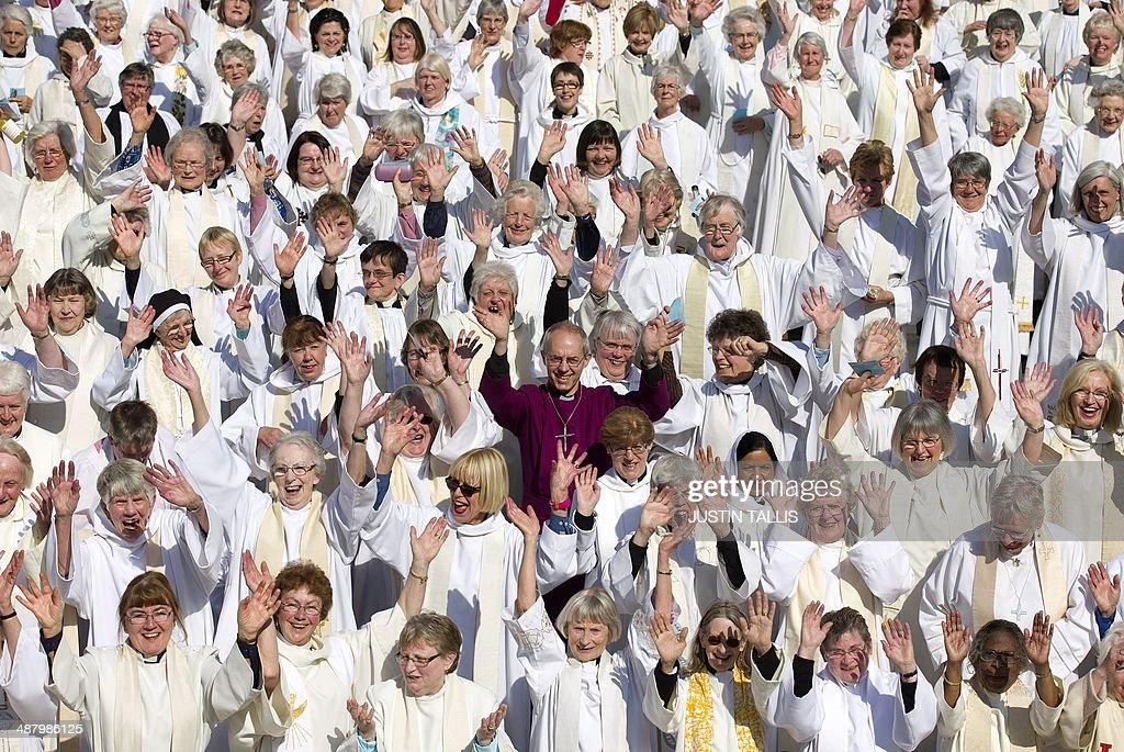 Archbishop of Canterbury Justin Welby poses for pictures with women priests on the steps of St Paul's Cathedral in London on May 3 to mark the...