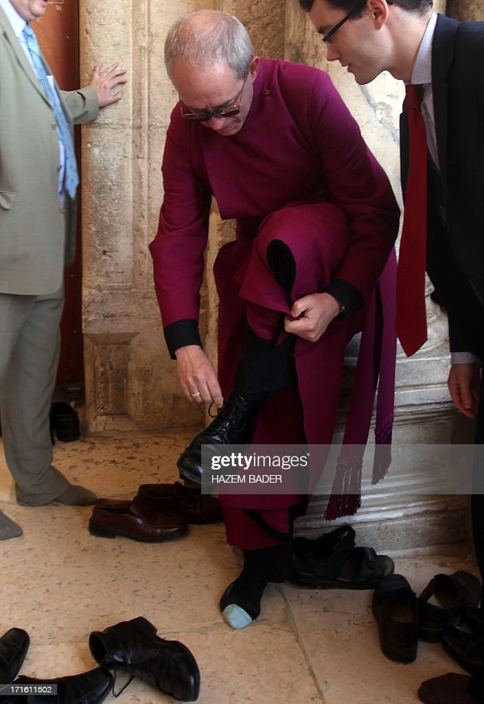 Archbishop of Canterbury Justin Welby (C), the spiritual leader of the Church of England, takes off his shoe before entering the al-Aqsa mosque in Jerusalem's Old City, on June 27, 2013. The leader of the world's Anglicans will visit the Western Wall, the Church of the Holy Sepulchre and the Temple Mount, as well as Israel's Yad Vashem Holocaust memorial. AFP PHOTO/HAZEM BADER