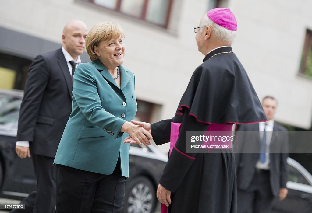 Archbishop of Freiburg and head of the German Bishops' Conference Robert Zollitsch welcomes German chancellor <a gi-track='captionPersonalityLinkClicked' href=/galleries/search?phrase=Angela+Merkel&family=editorial&specificpeople=202161 ng-click='$event.stopPropagation()'>Angela Merkel</a> at annual St. Michael Meeting of German Bishops' conference on September 02, 2013 in Berlin, Germany.