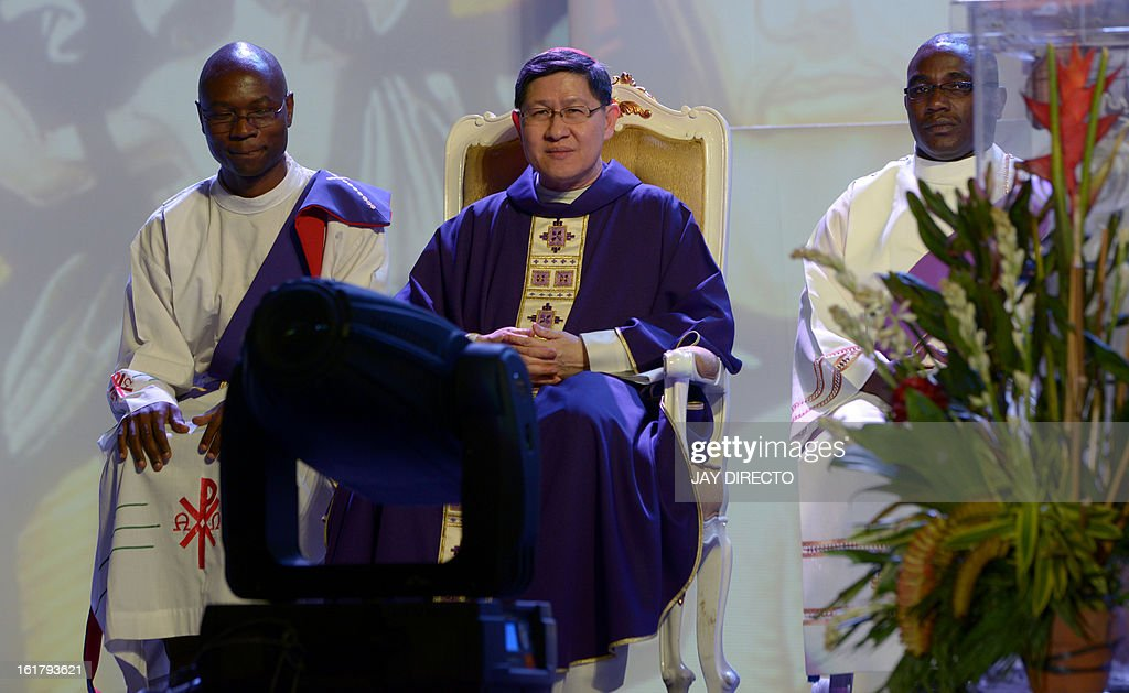 Archbishop of Manila Cardinal Luis Antonio Tagle (C) sits during a mass at a Catholic gathering in Manila on February 16, 2013. Filipinos are hoping that 55-year-old Tagle, who was only made a cardinal last year, could become the next pope following the shock announcement by 85-year-old Pope Benedict XVI that he would resign because of health reasons. AFP PHOTO / Jay DIRECTO