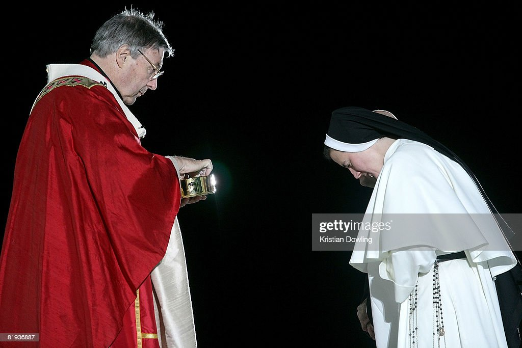 Archbishop of Sydney Cardinal George Pell AC (L) performs the Eucharist for a Nun on stage at the Opening Mass formally celebrating the start of World Youth Day 2008 at Barangaroo on July 15, 2008 in Sydney, Australia. Organised every two to three years by the Catholic Church, World Youth Day (WYD) is an invitation from the Pope to the youth of the world to celebrate their faith. The celebration, being held in Sydney from July 15 to July 20, 2008, will mark the first visit of His Holiness Pope Benedict XVI to Australia.