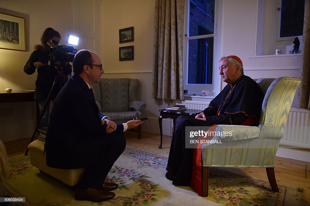 Archbishop of Westminster, Cardinal Vincent Nichols (R) gives an interview ahead of a service at Hampton Court Palace, in south west London on February 9, 2016. The sounds of Latin song will echo through the halls of Hampton Court Palace in London on Tuesday for the first Catholic service in more than 450 years to be held in anti-Vatican king Henry VIII's residence. Cardinal Vincent Nichols, head of the Catholic Church in England, celebrates the Vespers with Anglican Bishop of London Richard Chartres in a symbolic gesture of reconciliation between the two churches. / AFP / Ben STANSALL