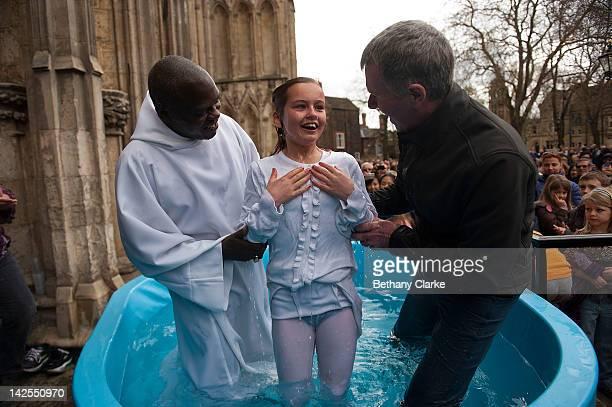 Archbishop of York Dr John Sentamu baptises Santa Mezaka 12 in a water tank during an Easter Saturday ceremony on April 7 2012 in York England...