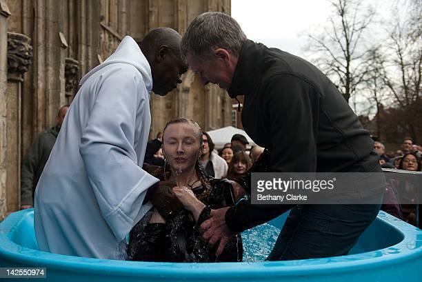 Archbishop of York Dr John Sentamu lifts up from the water tank a local church goer as he baptises the new Christian during an Easter Saturday...