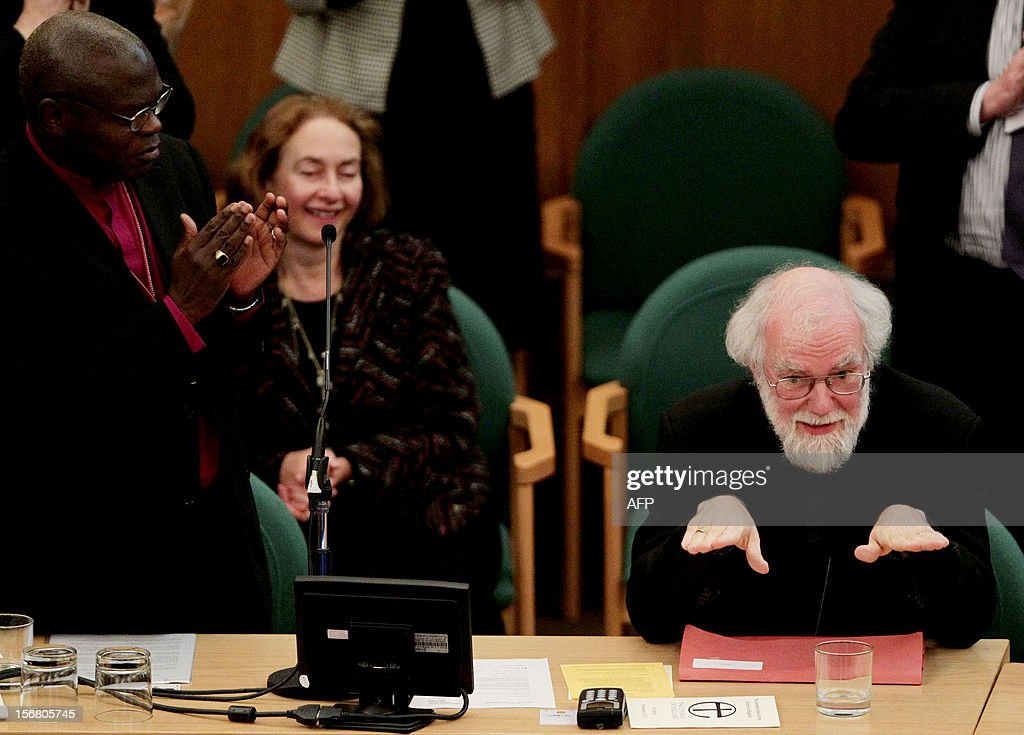 Archbishop of York John Sentamu (L) applauds outgoing Archbishop of Canterbury Rowan Williams (R) during a meeting at the General Synod of the Church of England, at Church House in central London on November 21, 2012. The Church of England has 'undoubtedly' lost credibility after voting to reject the appointment of women bishops, its leader the Archbishop of Canterbury said on November 21.