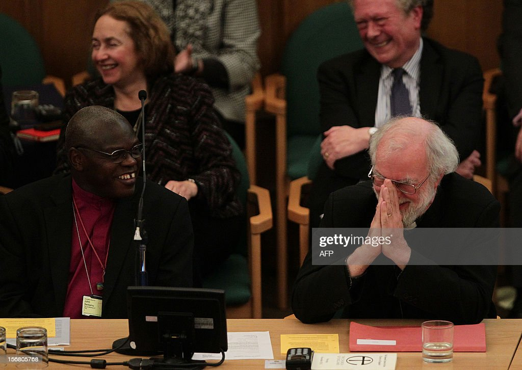 Archbishop of York John Sentamu (L) laughs with outgoing Archbishop of Canterbury Rowan Williams (R) as they pay farewell tributes to him during a meeting at the General Synod of the Church of England, at Church House in central London on November 21, 2012. The Church of England has 'undoubtedly' lost credibility after voting to reject the appointment of women bishops, its leader the Archbishop of Canterbury said on November 21. AFP PHOTO / POOL / YUI MOK