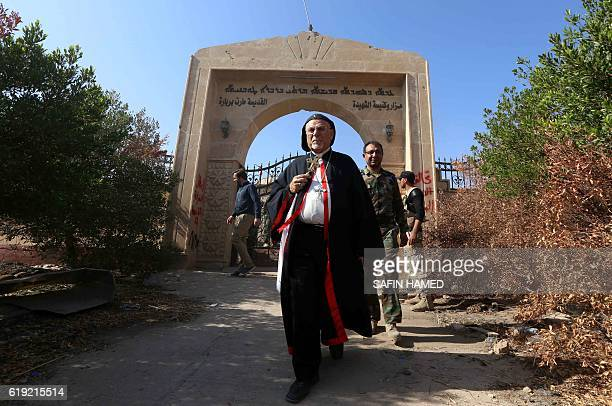 Archbishop Yohanna Petros Mouche of Mosul inspects the damage at the Saint Barbara Church on October 30 2016 in the town of Qaraqosh 30 kms east of...