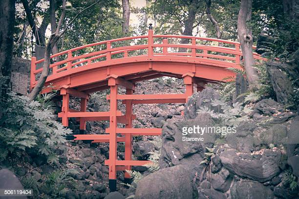 Arched Orange Bridge In Japanese Garden
