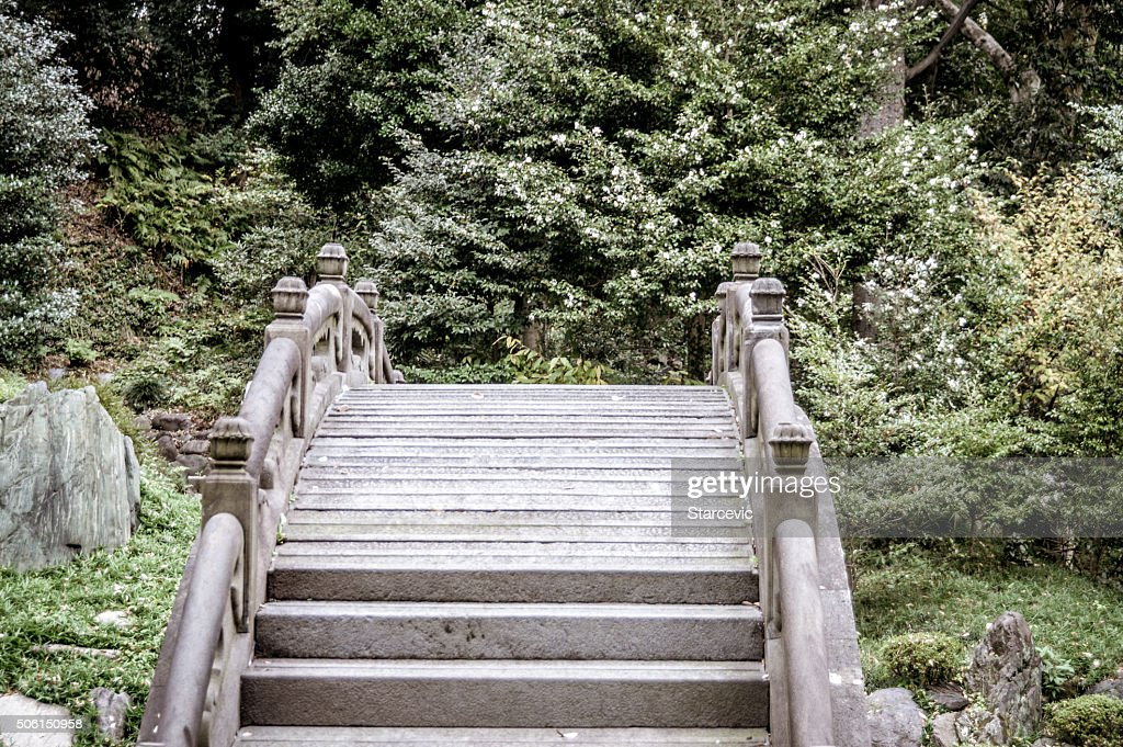 arched stone bridge in japanese garden stock photo