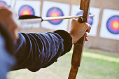 close up image of Archer holds his bow aiming at a target