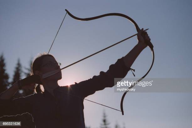 Archer shooting with a bow in the mountains.