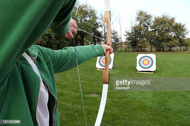 Archery firing at targets on a grass field