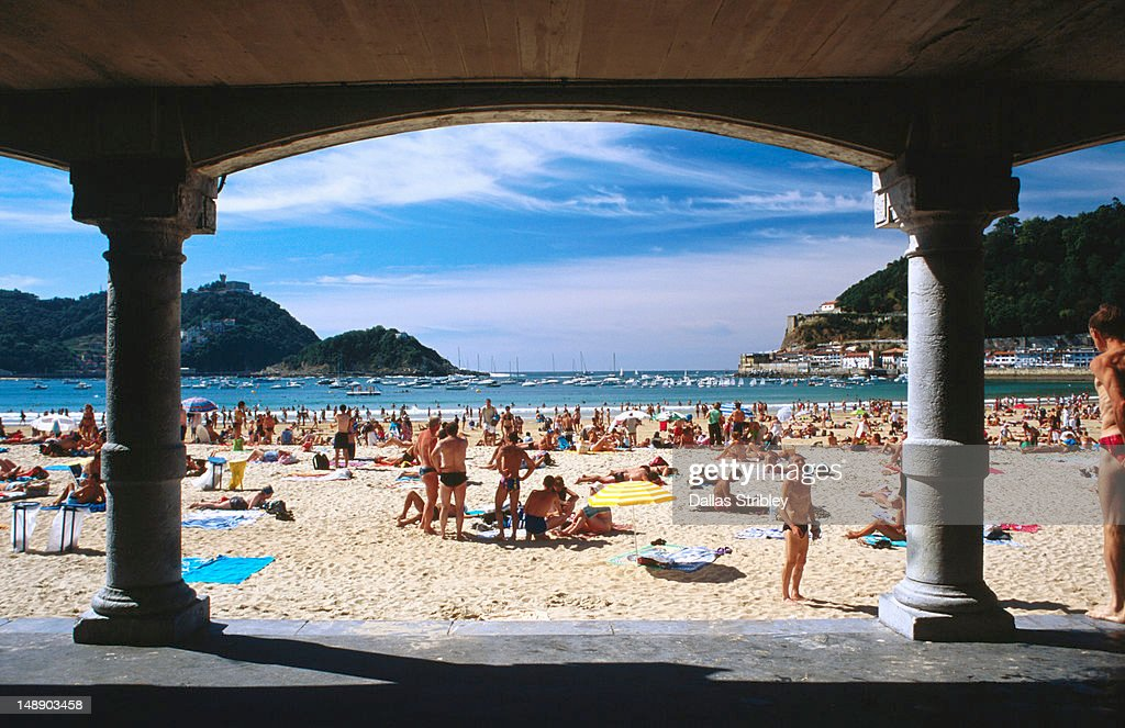 Arches frame people at Playa de la Concha on summer's day. : Stock Photo