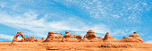 Panorama of Arches National Park with the world famous Delicate Arch on the left on a sunny summer day, Utah, USA.