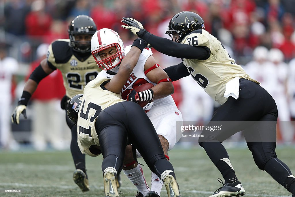 Archibald Barnes #15 and Chase Garnham #36 of the Vanderbilt Commodores tackle Quintin Payton #88 of the North Carolina State Wolfpack during the Franklin American Mortgage Music City Bowl at LP Field on December 31, 2012 in Nashville, Tennessee.