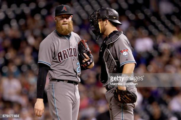Archie Bradley and Jeff Mathis of the Arizona Diamondbacks confer in the ninth inning against the Colorado Rockeis at Coors Field on May 5 2017 in...