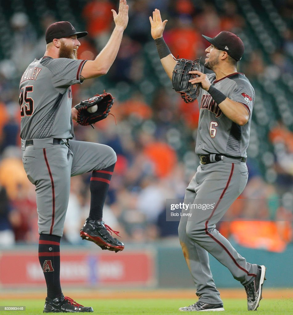 Archie Bradley #25 of the Arizona Diamondbacks high fives David Peralta #6 after the final out of the game against the Houston Astros at Minute Maid Park on August 17, 2017 in Houston, Texas.