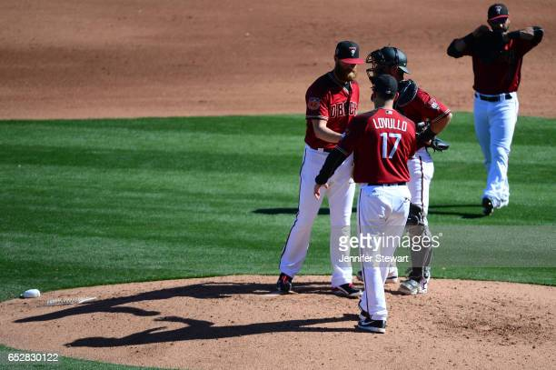 Archie Bradley of the Arizona Diamondbacks is relieved by manager Torey Lovullo during the spring training game against the Colorado Rockies at Salt...