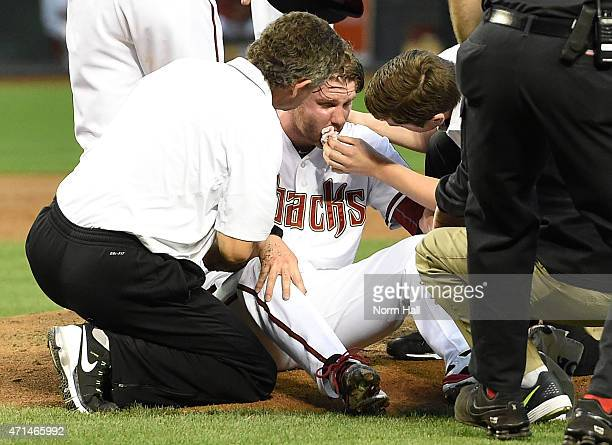 Archie Bradley of the Arizona Diamondbacks is tended to on the pitcher's mound after getting hit in the face with a line drive against the Colorado...
