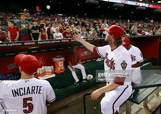 Archie Bradley of the Arizona Diamondbacks tosses an autographed ball to a young fan before the start of a MLB game against the Colorado Rockies at...