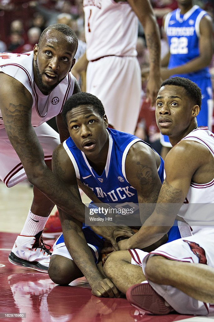 Archie Goodwin #10 of the Kentucky Wildcats, Marshawn Powell #33 and Anthlon Bell #5 of the Arkansas Razorbacks look at the official for a call on a loose ball at Bud Walton Arena on March 2, 2013 in Fayetteville, Arkansas. The Razorbacks defeated the Wildcats 73-60.