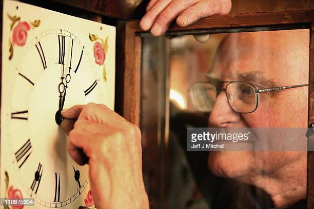 Archie McQuater 82yearold clockmaker at Craiglea clocks adjusts a clock face to British Summer Time on March 25 2011 in Edinburgh Scotland Clocks...