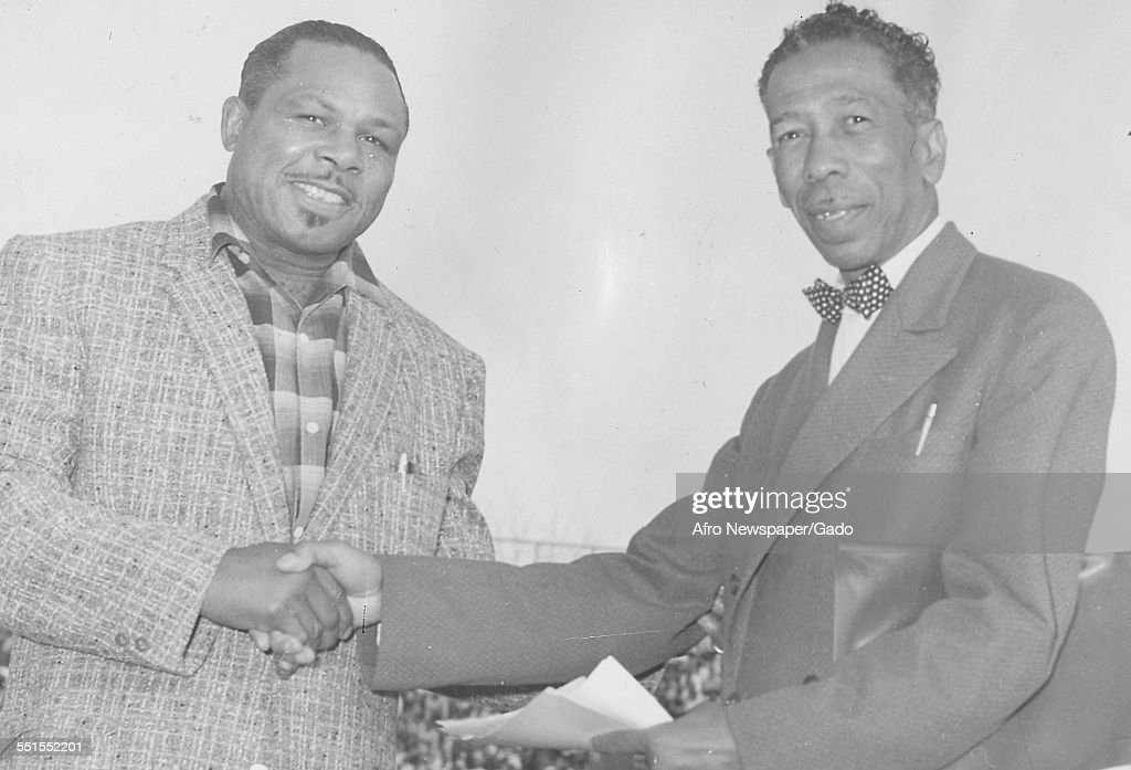 <a gi-track='captionPersonalityLinkClicked' href=/galleries/search?phrase=Archie+Moore&family=editorial&specificpeople=93092 ng-click='$event.stopPropagation()'>Archie Moore</a>, African-American professional boxer and the Light Heavyweight World Champion, shaking hands with a man, 1955.