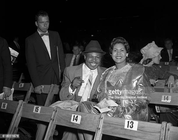Archie Moore and his wife are one of the many spectators at the Carmen Basilio vs Sugar Ray Robinson middleweight title fight in Bronx New York...
