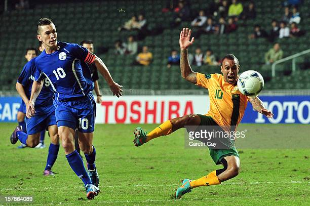 Archie Thompson of Australia is tackled by Jason Cunliffe of Guam during the EAFF East Asian Cup 2013 Qualifying match between Guam and Australia at...