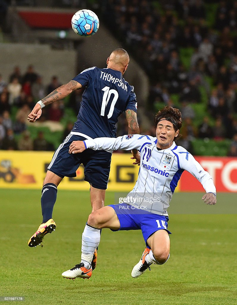 Archie Thompson (L) of Melbourne Victory and Koki Yonekura (R) of Gamba Osaka fight for the ball during the AFC Champions League football match between Melbourne Victory and Gamba Osaka in Melbourne on May 3, 2016. / AFP / Paul Crock / IMAGE