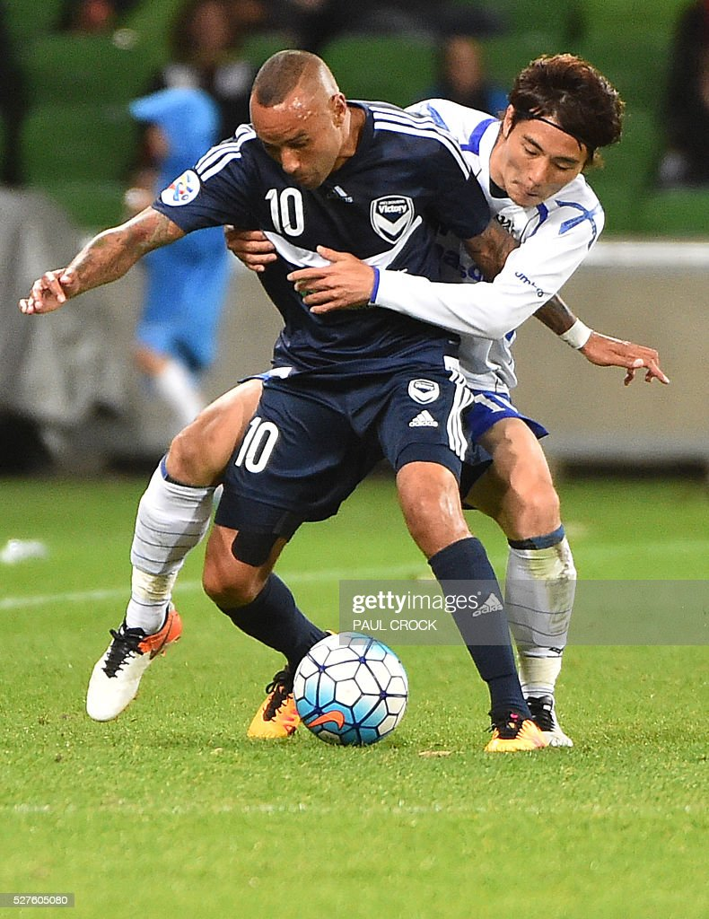 Archie Thompson (L) of Melbourne Victory and Koki Yonekura (R) of Gamba Osaka fight for the ball during the AFC Champions League football match between the Melbourne Victory and Gamba Osaka in Melbourne on May 3, 2016. / AFP / Paul Crock / IMAGE