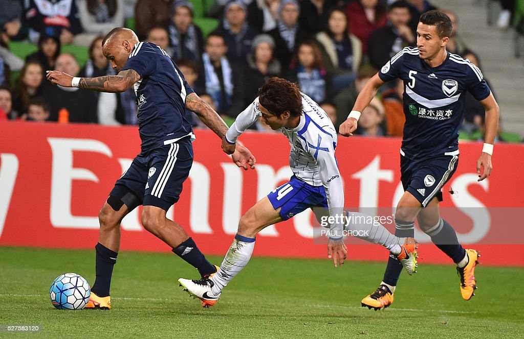 Archie Thompson (L) of Melbourne Victory outruns Koki Yonekura (C) of Gamba Osaka during the AFC Champions League football match between Melbourne Victory and Gamba Osaka in Melbourne on May 3, 2016. / AFP / Paul Crock
