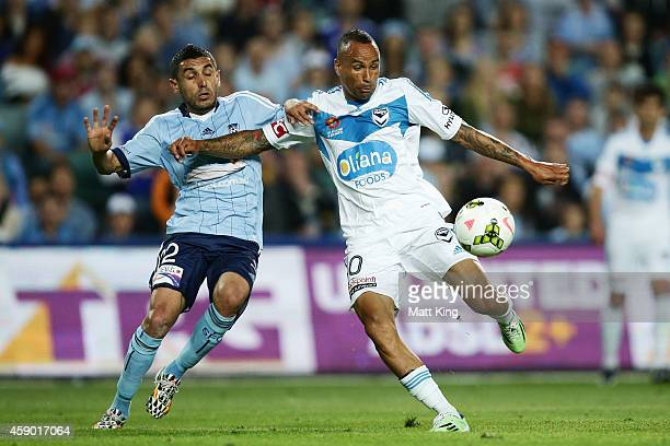Archie Thompson of Melbourne Victory takes a shot on goal next to Ali Abbas of Sydney FC during the round six ALeague match between Sydney FC and...