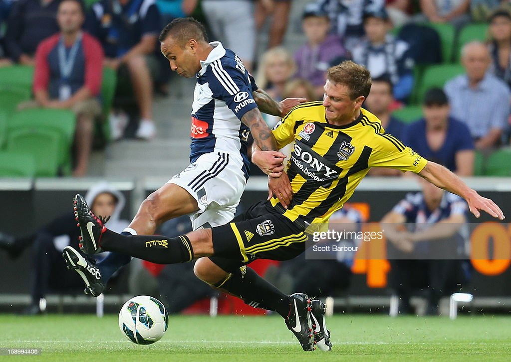 Archie Thompson of the Victory and Ben Sigmund of the Phoenix compete for the ball during the round 15 A-League match between the Melbourne Victory and Wellington Phoenix at AAMI Park on January 5, 2013 in Melbourne, Australia.