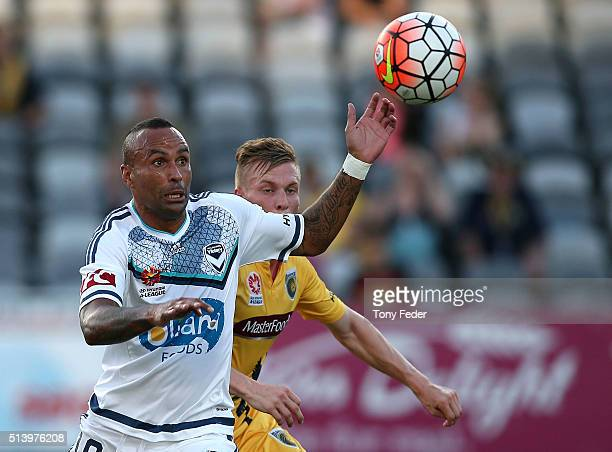 Archie Thompson of the Victory contests the ball with his Mariners opponent during the round 22 ALeague match between the Central Coast Mariners and...