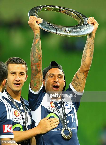 Archie Thompson of the Victory holds the trophy aloft after the Victory won the 2015 ALeague Grand Final match between the Melbourne Victory and...