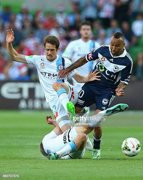 Archie Thompson of the Victory is tackled by Mate Dugandzic and Jacob Melling of City during the round 12 ALeague match between Melbourne City FC and...